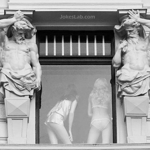 funny statue staring at  sexy girls